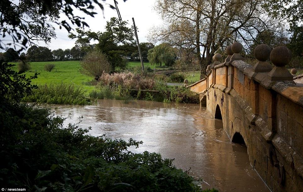 The swollen River Stour flows underneath a bridge in Tredington, Warwickshire