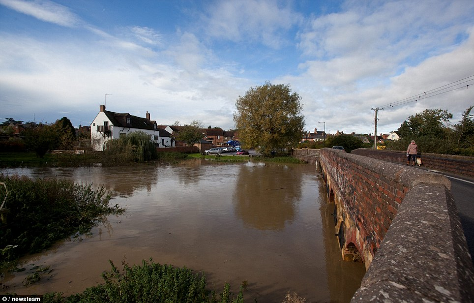 A lone walker makes their way across a bridge over the River Stour, in Warwickshire, after the heavy rainfall