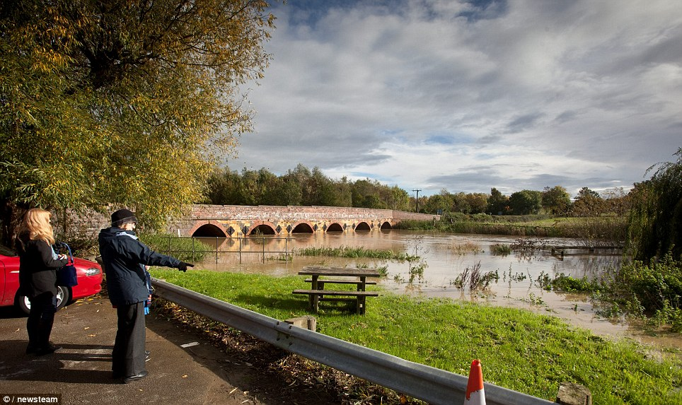 Passers-by survey the damage to the Rover Stour in Warwickshire. A flood warning is one step up from an alert, and is in place to tell people that flooding is expected, and immediate action should be taken