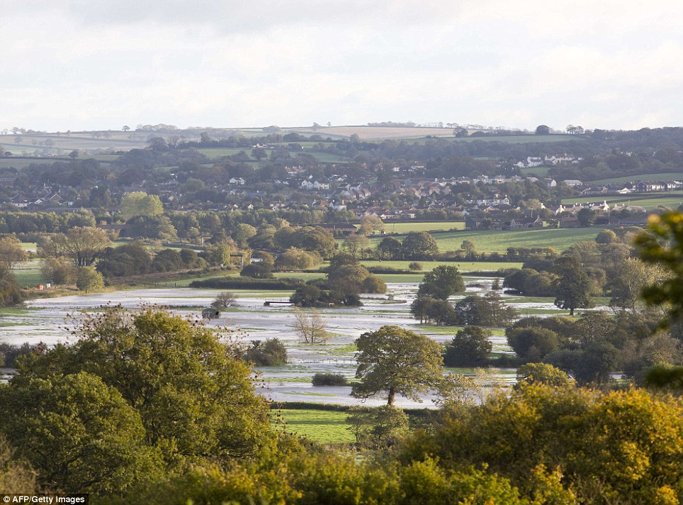Flooded fields near the village of Whitford, near Devon. Britain faced travel chaos on October 28 and over 200,000 homes were without power as one of the worst storms in years battered southern England, sweeping at least one person out to sea