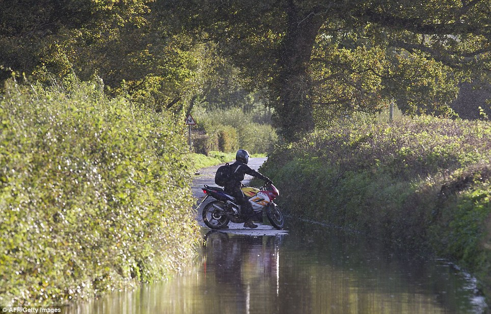 A motorcycle rider decides to turn back from a flooded area of road near the village of Whitford, in Devon