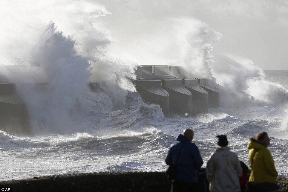 People watch the waves batter into the sea wall of a marina in Brighton