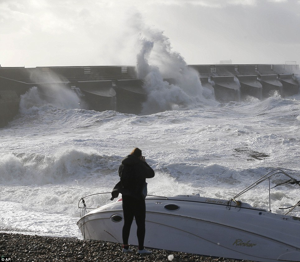 A boat lays stricken on the beach as people watch the waves batter into the sea wall of a marina in Brighton