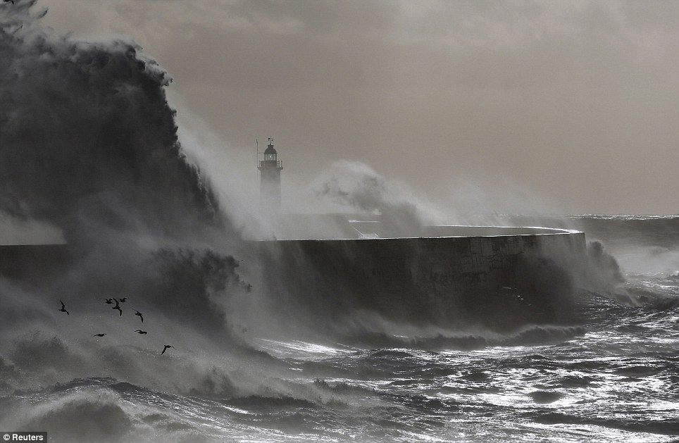 Waves crash against a lighthouse during storms that battered Britain and where a 14-year-old boy was swept away to sea at Newhaven