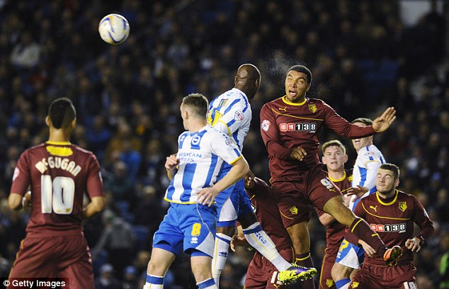Aerial duel: Watford striker Tory Deeney rises above Brighton's Leroy Lita to clear the ball away from danger