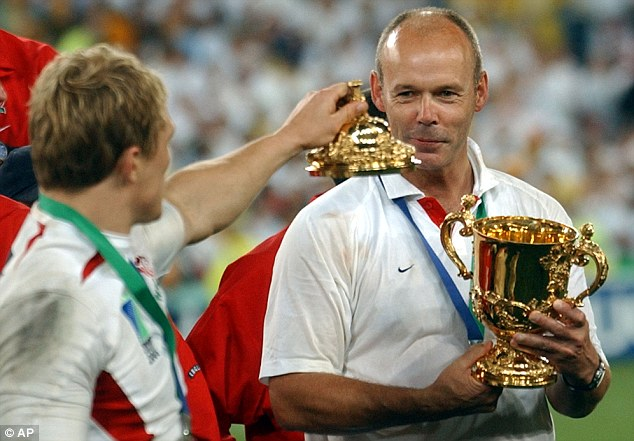 Clive Woodward holds the Webb Ellis Cup as Jonny Wilkinson picks up the lid