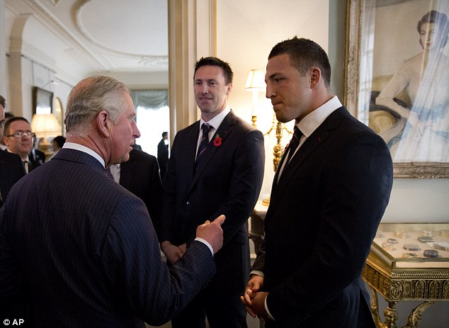 Warm welcome: The Prince chats with England star Sam Burgess (right) at Clarence House