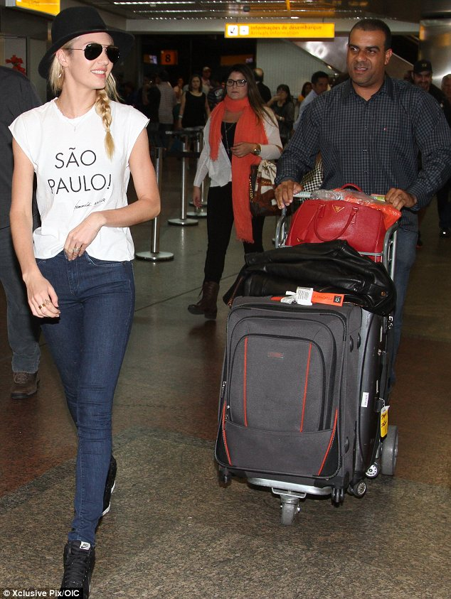 Getting a little help: Candice Swanepoel needed assistance with her luggage when she arrived in Sao Paolo