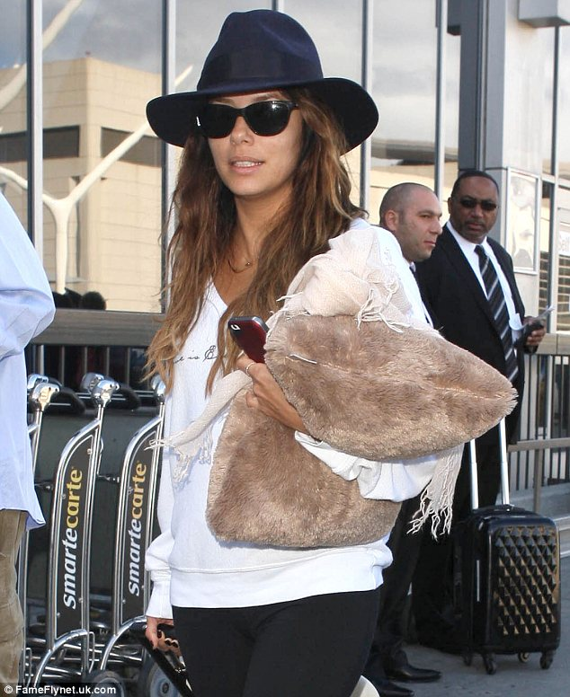 Dressed for comfort: Eva was dressed down in leggings and a white sweater and carried her favourite travel pillow at LAX
