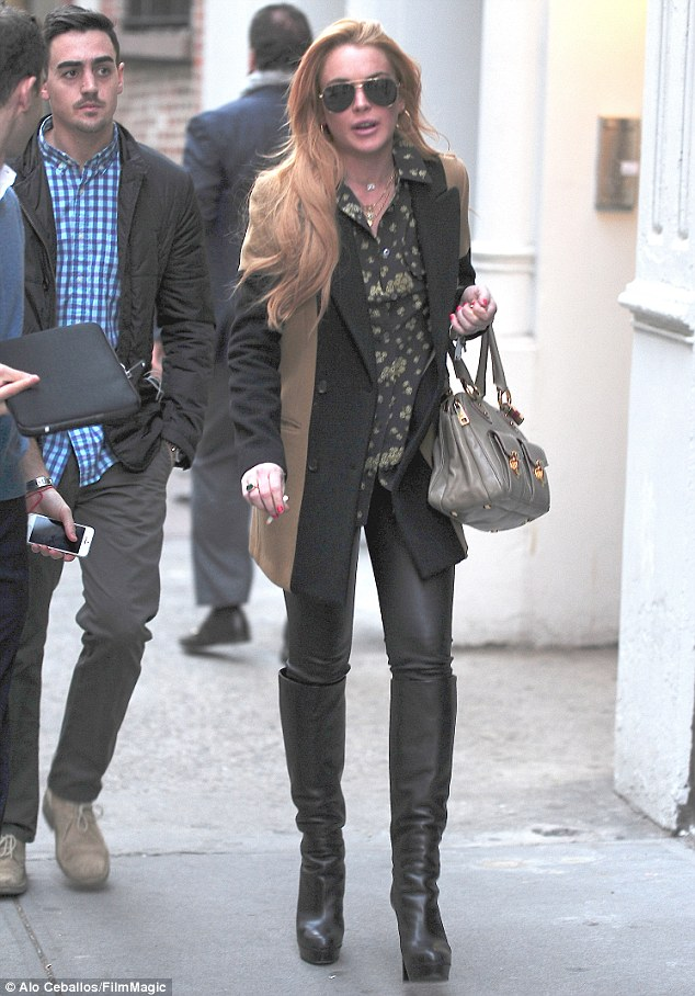 In the big smoke: Lindsay looks well-groomed as she strolls around Soho in New York on Monday but she can't resist a cheeky cigarette