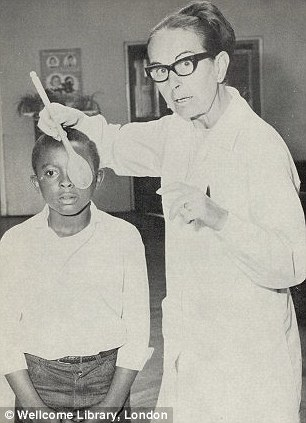 1971: This young boy has his eyes tested in Lewisham, south-east London, using a wooden spoon to obscure the eye