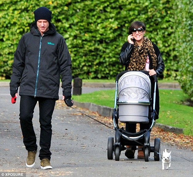 Happy families: Frankie Sandford takes a stroll with partner Wayne Bridge and their baby son Parke in London on Wednesday