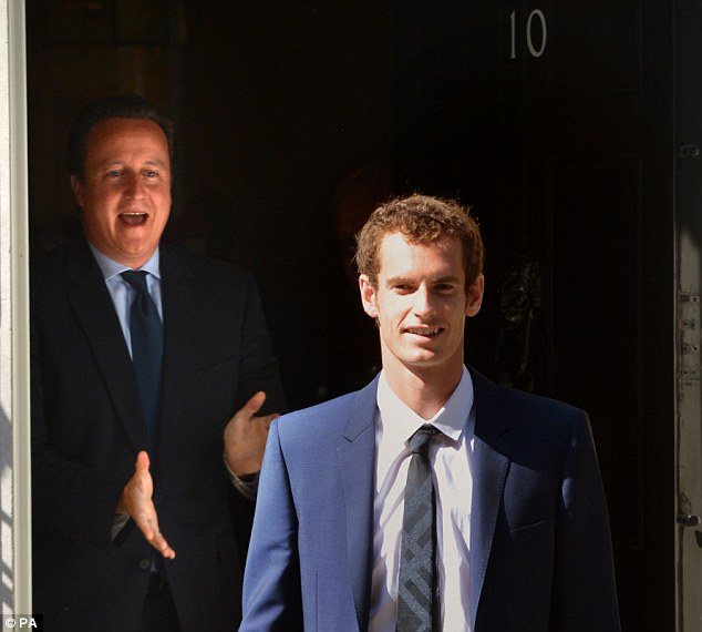 Andy Murray poses for photographs outside 10 Downing Street on the day after winning Wimbledon as Prime Minister David Cameron opens the door