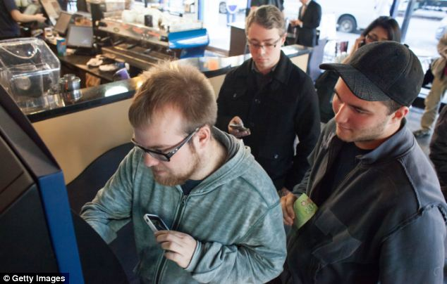 Curtis Machek, left, uses the world's first bitcoin ATM at Waves Coffee House in Canada. 'It was so easy,' he said. 'I wanted to try out this new machine that hopefully will change the world.'