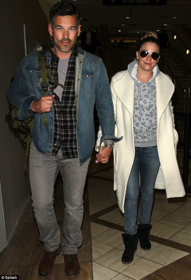 Nothing to see here: The couple appeared to be trying to quash the rumours when they were spotted walking hand-in-hand after landing at LAX airport in Los Angeles on Tuesday