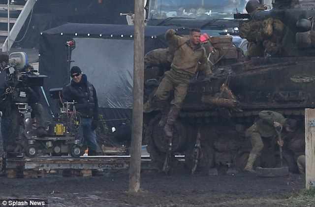 Messy business: The actor jumps into a muddy field during a break in filming