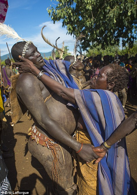 A Bodi woman wipes away the sweat of one of the fat men