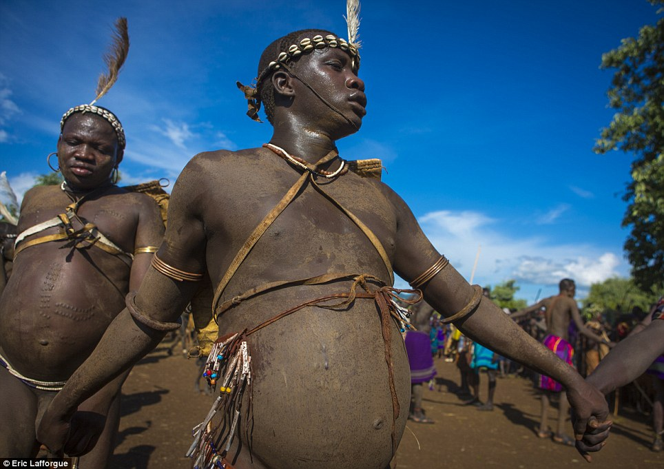 Sacred: The fat men run or walk around the village's special tree, watched by the tribe's elders and other men, and helped by the women