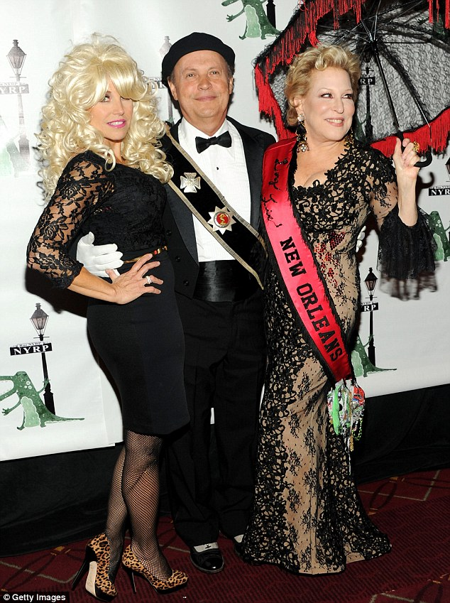 Lucky man: Billy Crystal was flanked during his photo op by both Katie and Bette
