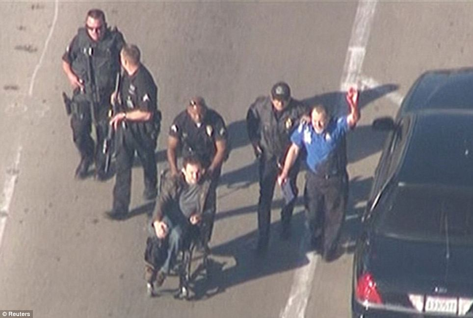 Treating the injured: A visibly injured TSA  agent is escorted out by responding officers as well as a man in a wheelchair. It is unclear what exactly happened to the TSA agent and it is not known if he was one of the agents who was shot by the gunman