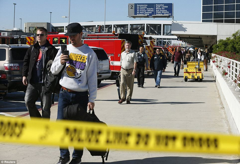 Emergency crews set up outside of LAX as passengers evacuate the area following the shooting at around 10am on Friday morning