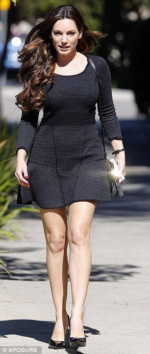 Leggy lady: Kelly showed off her enviable figure in the long-sleeved dress as she strutted her stuff on the sidewalk