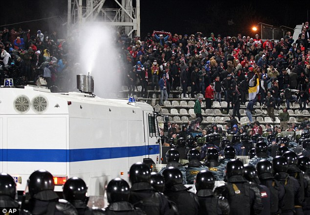 Flaring up: Riot police use a water cannon (below) to bring the trouble under control in Yaroslavl