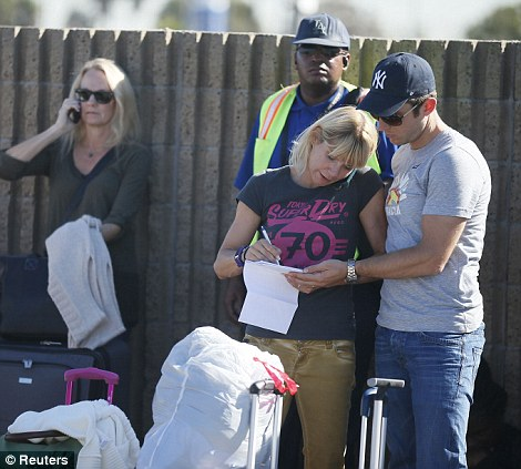 Passengers pictured at LAX today following the fatal shooting at Terminal 3. The airport was placed on lock down and flights redirected to other airports