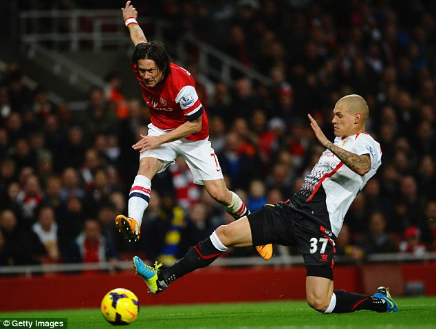 Straining: Tomas Rosicky tries to play the ball up the line under pressure from Martin Skrtel