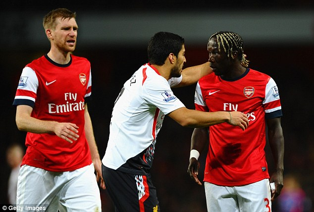 Causing trouble: Suarez and Bacary Sagna have a disagreement late on