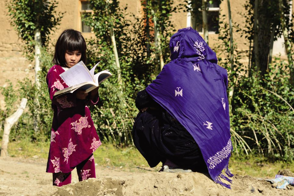 Studying: A young girl reads in the sunshine