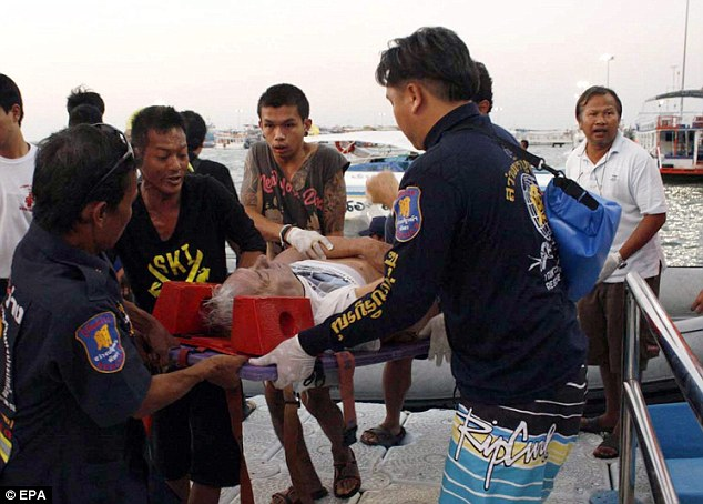 Aid: Thai rescue workers and medics carry an injured tourist on a stretcher after a ferry sank off Pattaya
