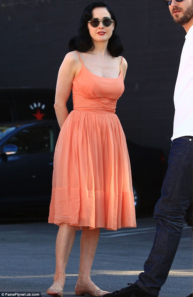 Spectator sport: Delta's pal Dita Von Teese opted to watch from the sidelines, looking chic in her orange dress