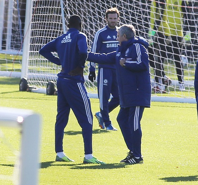 Hands on: Mourinho (right) shows Demba Ba (left) what to do as Juan Mata looks on