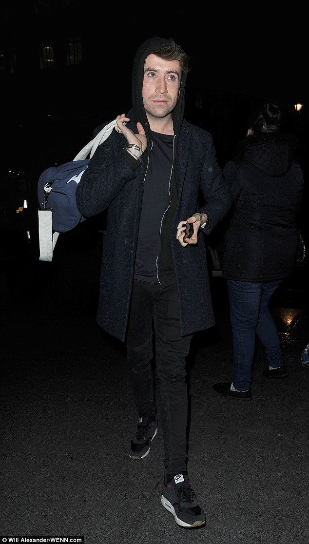 Bleary eyed: Nick Grimshaw looked casual in black jeans, T-shirt, and Nike trainers, with a coat and hoodie layered up and with the hood up to keep out the cold November chill