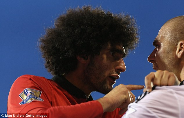 Hair-raising: Marouane Fellaini (left) clashes with Philippe Senderos during Manchester United's win at Fulham