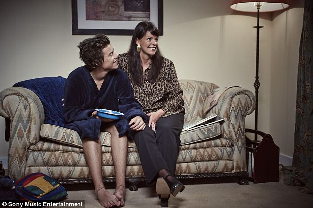 Family time: Harry Styles relaxes on the sofa in a blue velveteen dressing gown