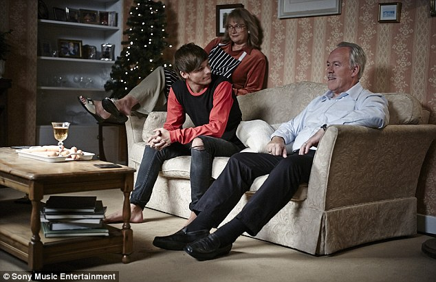 Tea time: Louis Tomlinson enjoys a TV dinner at home