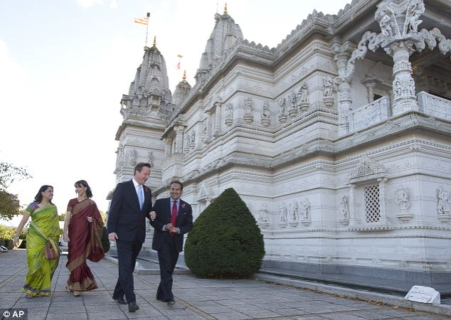 Britain's Prime Minister David Cameron, second right, Vinu Bhattessa, a trustee of the temple, right, Samantha Cameron, second left, and Rena Amin, a leading women's volunteer, walk past the Hindu temple