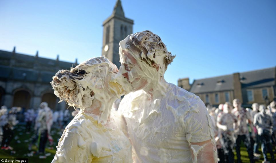 Romance: A couple lock lips as hundreds of freshers take part in a massive foam fight to mark the traditional student welcome at Scotland's oldest university