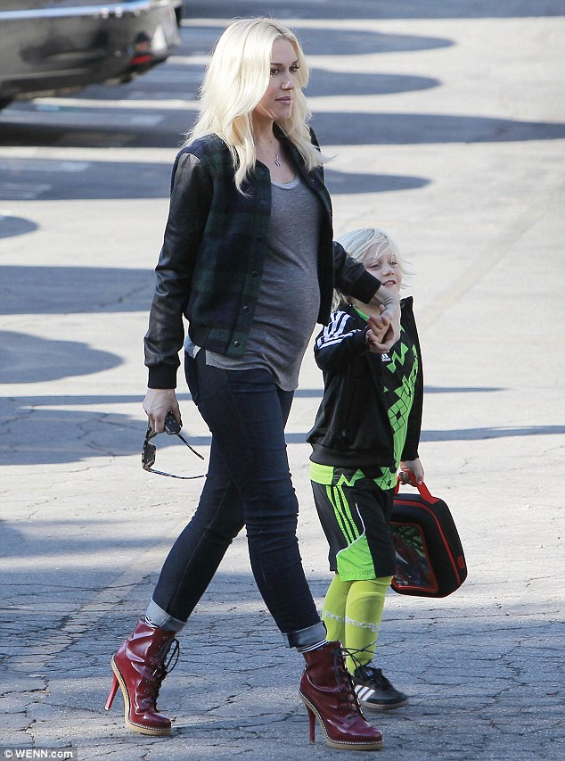 Hold on tight: The rockstar held her five-year-old son's hand as they made their way to the school building