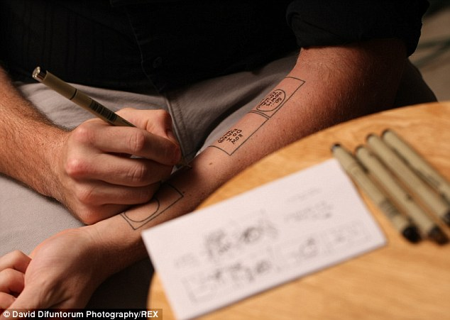Dedicated: Mr Yurick sits at his desk with his pens creating a new design on his tattooed arm