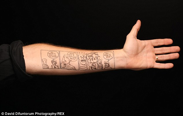 Patrick Yurick holds in his arm to show one of his creations on his tattooed arm