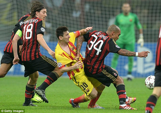 Crowded out: Nigel De Jong gets to grips with Messi during the game