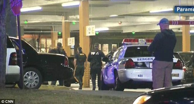 Police officers surround the mall where they were escorting terrified shoppers from the center with their arms in the air