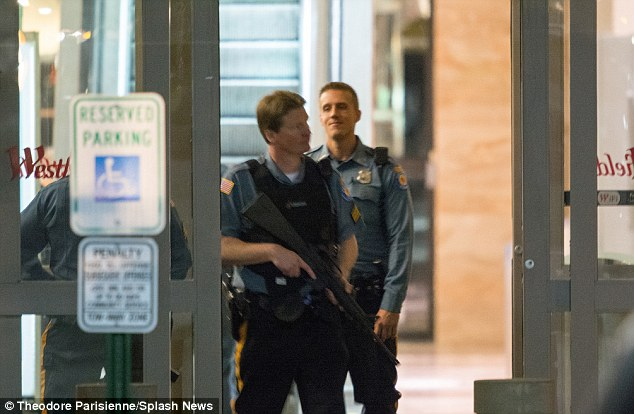 An armed policeman stands at the entrance to the Westfield shopping Mall during the hunt for the gunman