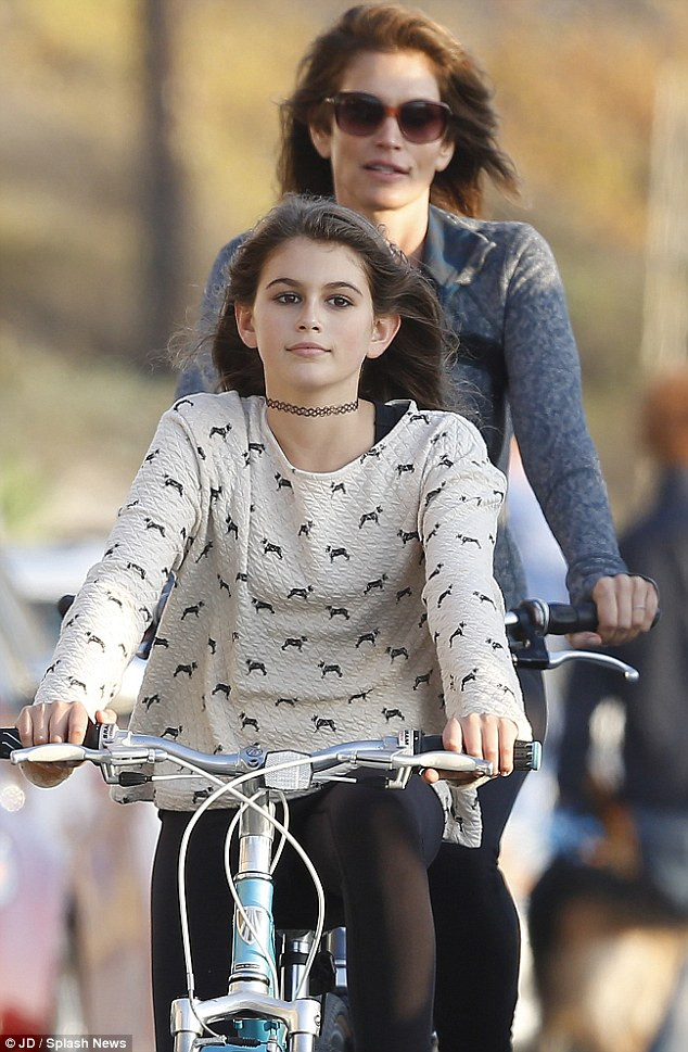Pedal power: The 47-year-old cycled behind her cute tween - who shares her incredible beauty and lush, dark hair - watching over the girl carefully