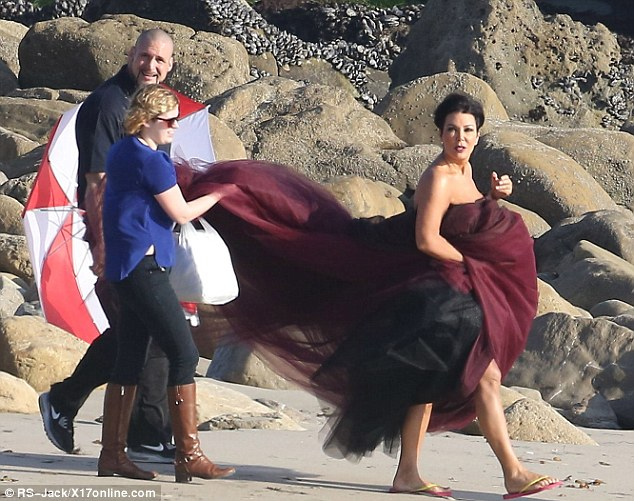 Going all out: Kris' dress was so big that she needed some help from assistants to get down to the beach