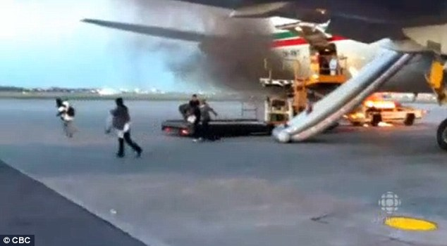 Slide of her life: A woman is seen sliding down the inflatable safety slide of the Boeing 767 as flames rage behind her