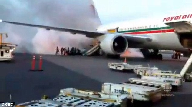 Big fire: Smoke can be seen billowing from the busy airport's tarmac as the blaze burns